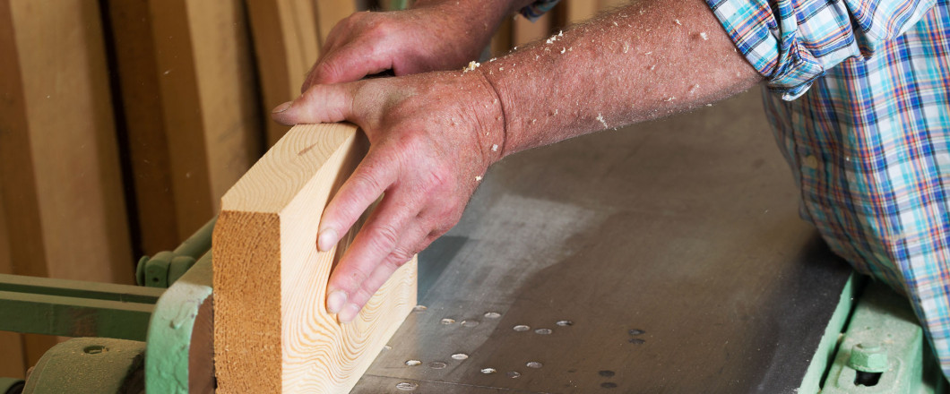 man's hands guiding wood through a table saw