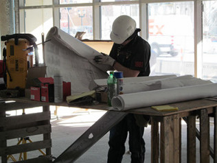 carpenter in hard hat looking through blueprints and plans