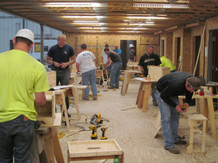 ten men in a workshop practicing carpentry